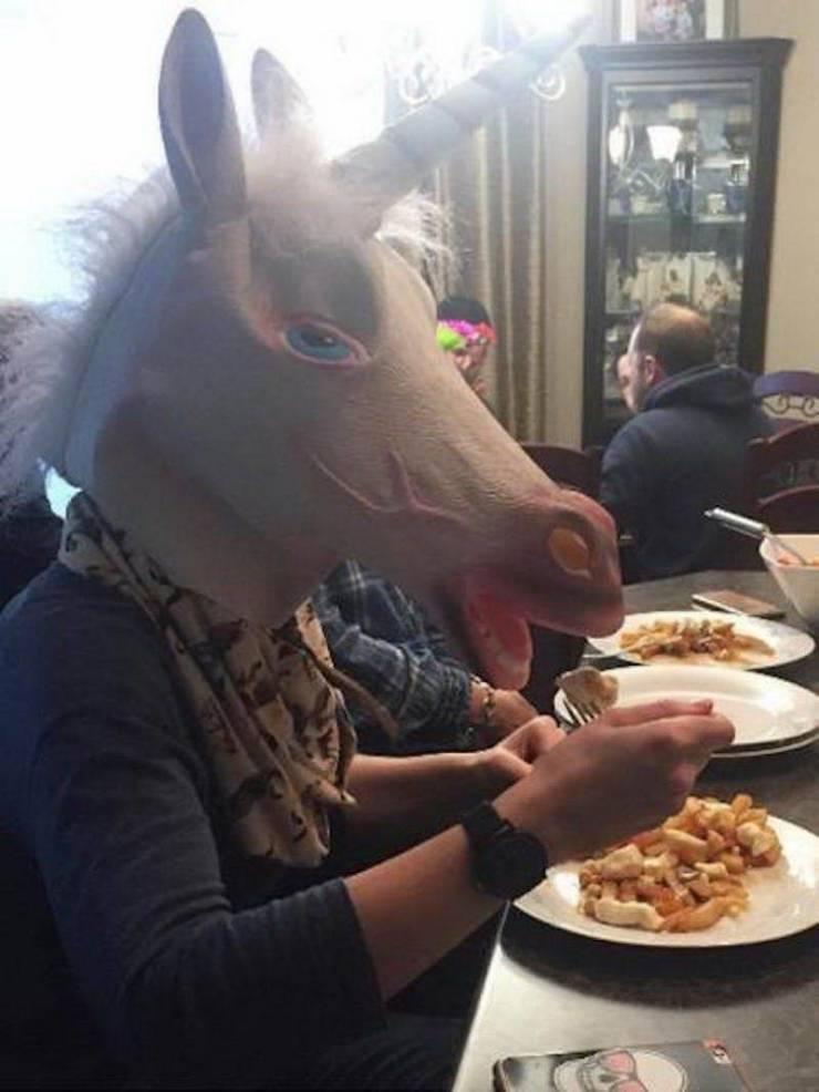 человек в маске единорога ест