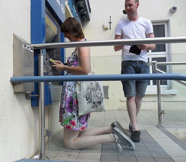 женщина стоит на коленях перед банкоматом