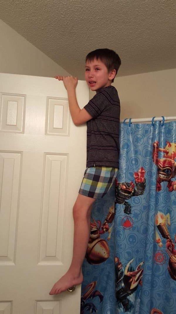 мальчик висит на двери