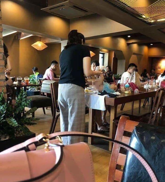 женщина меняет ребенку подгузник в ресторане