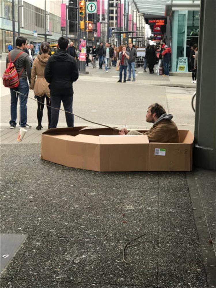 мужчина в картонной лодке просит милостыню