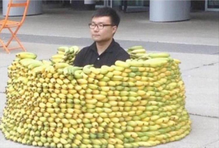мужчина сидит в куче бананов
