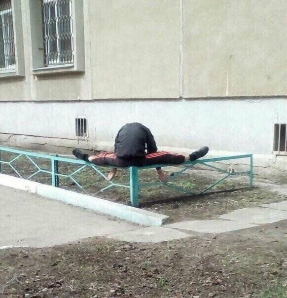 мужчина сидит на заборе