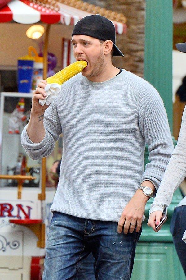 мужчина ест кукурузу