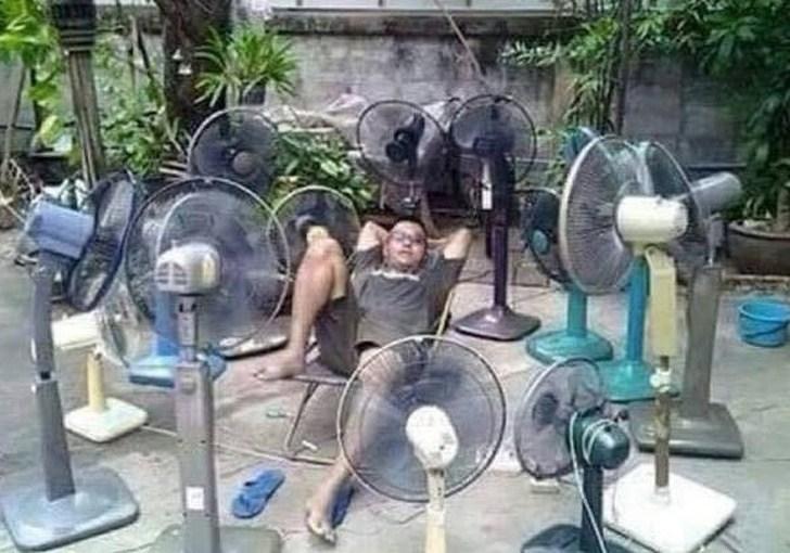 мужчина в окружении вентиляторов