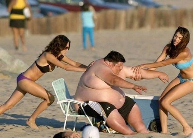девушки поднимают полного мужчину на пляже