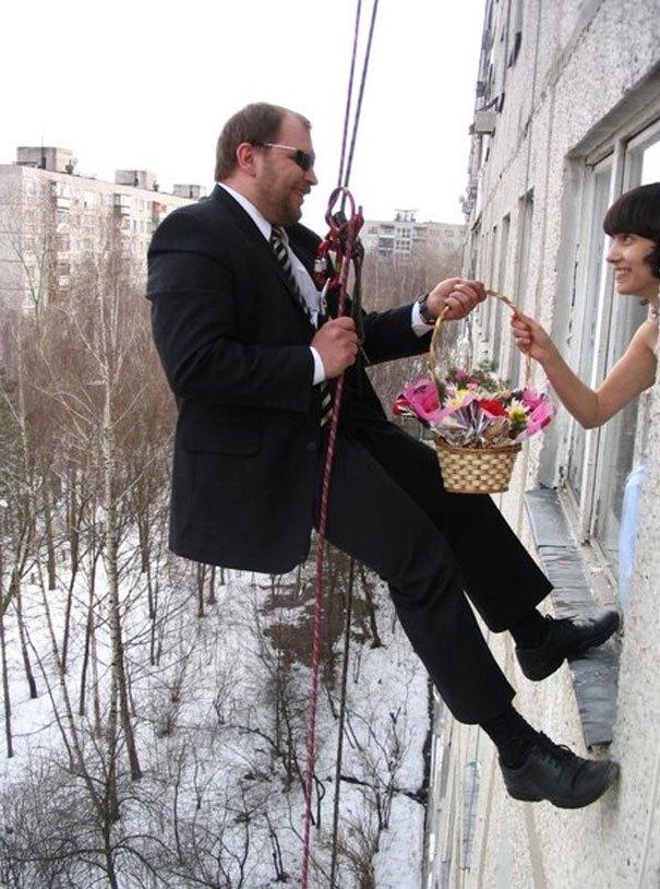 жених висит за окном с букетом