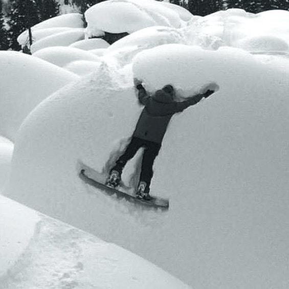 мужчина на сноуборде в сугробе