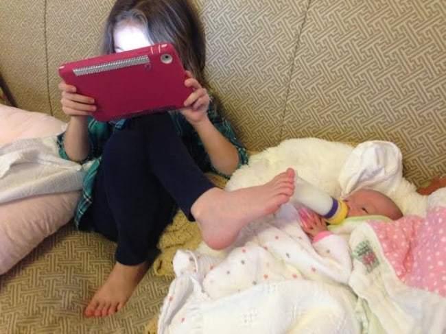 девочка с планшетом кормит ребенка