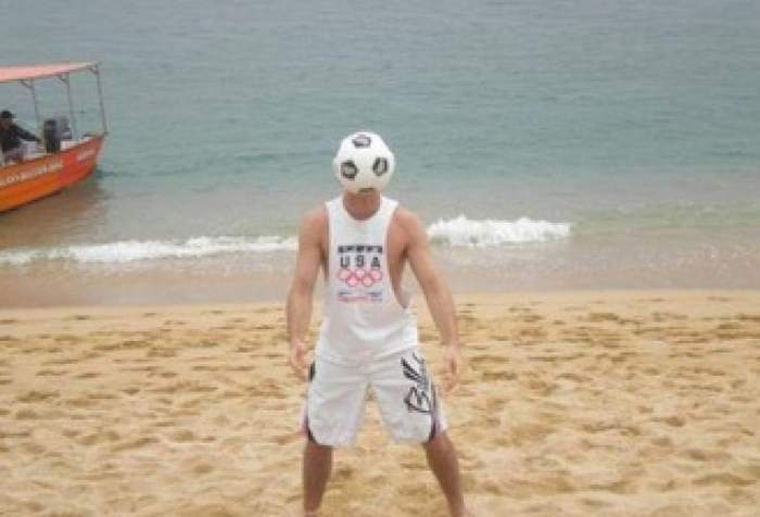 мужчина ловит мяч на пляже