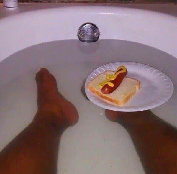 мужчина принимает ванну с бутербродом