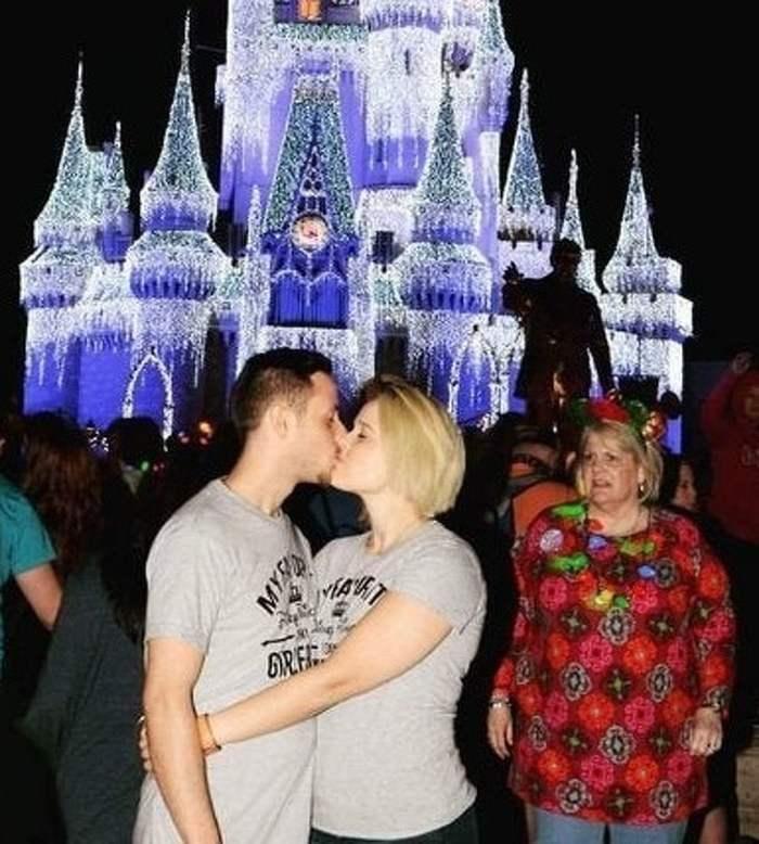 пара целуется напротив диснеевского замка