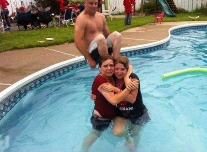 мужчина прыгает в бассейн с девушками