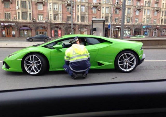 полицейский рядом со спорткаром