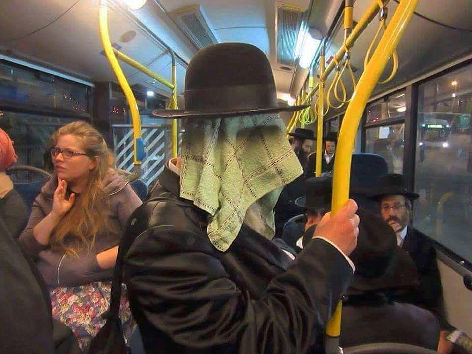 мужчина в шляпе с полотенцем на лице