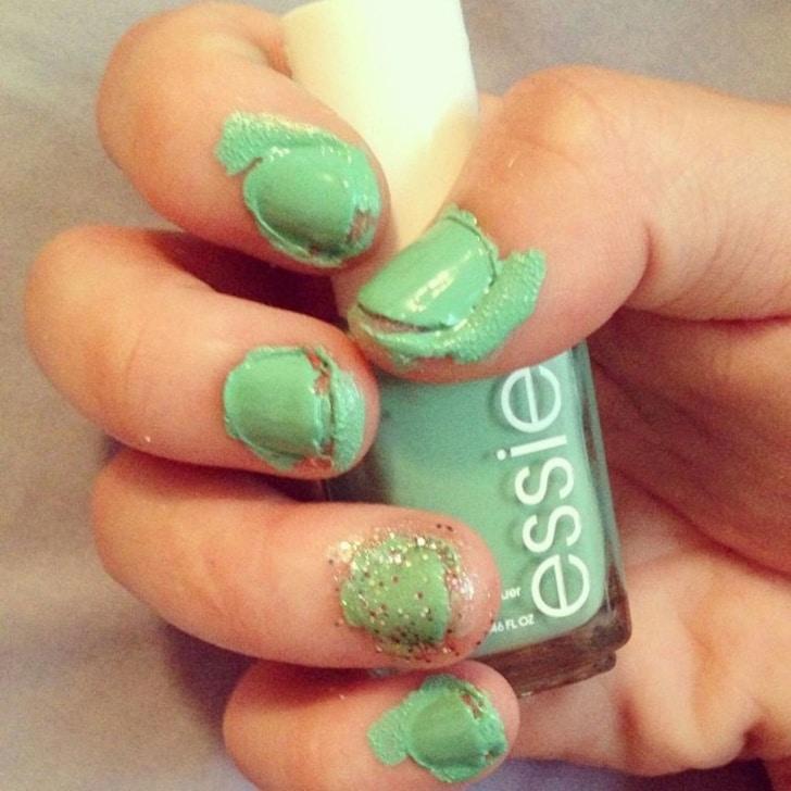 девушка держит в руке зеленый лак для ногтей