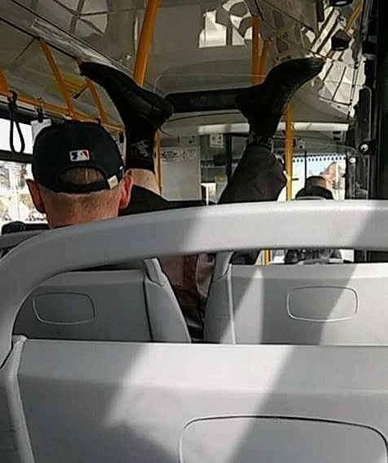 мужчина едет в автобусе с поднятыми вверх ногами