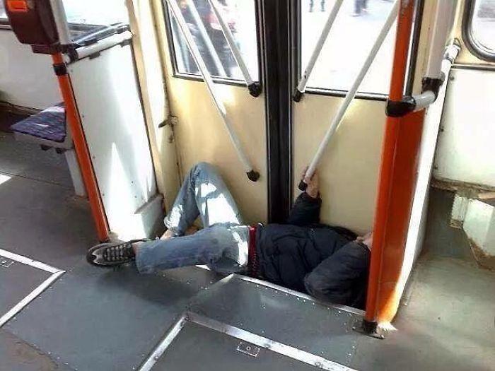 парень лежит на ступеньках в автобусе