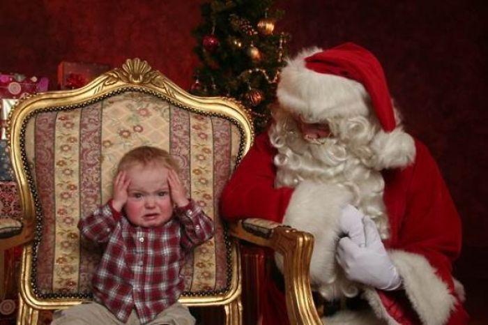 мальчик сидит в кресле рядом с дедом морозом