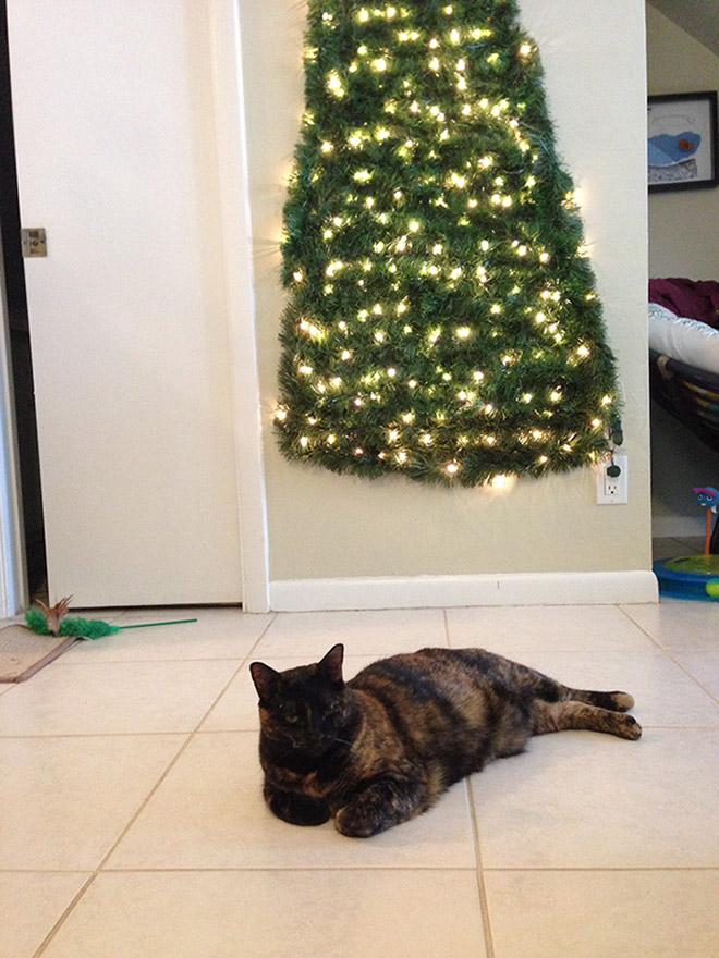 кошка лежит возле елки