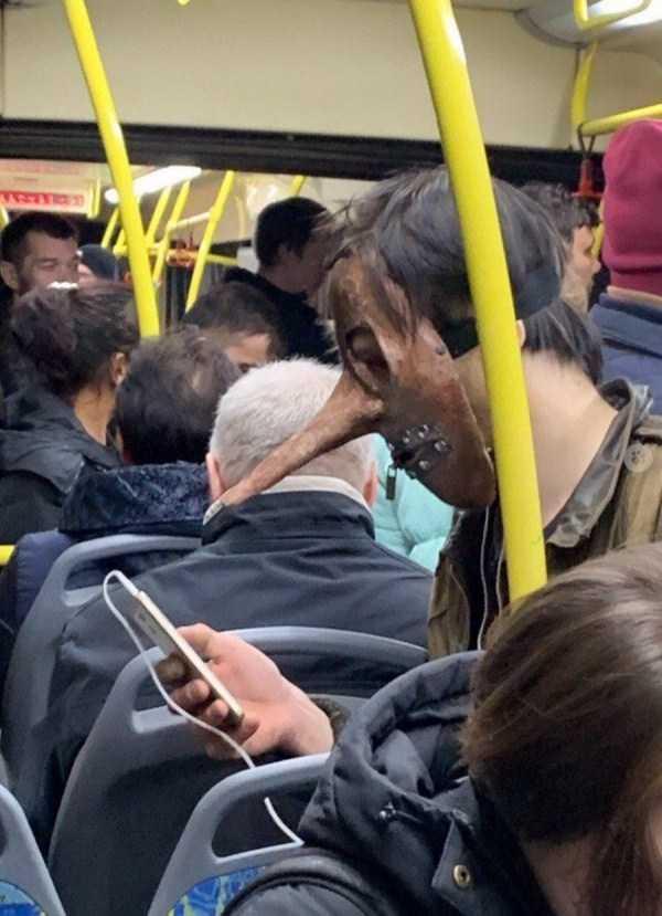 парень в маске с телефоном в метро
