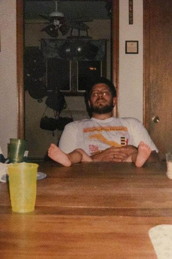 парень сидит за столом с ребенком на руках