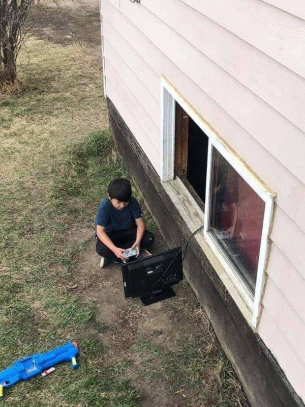 мальчик играет на компьютере за окном