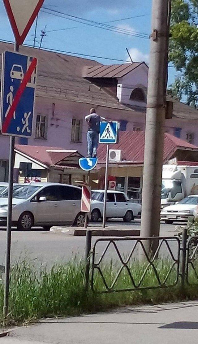 мужчина стоит на дорожном знаке