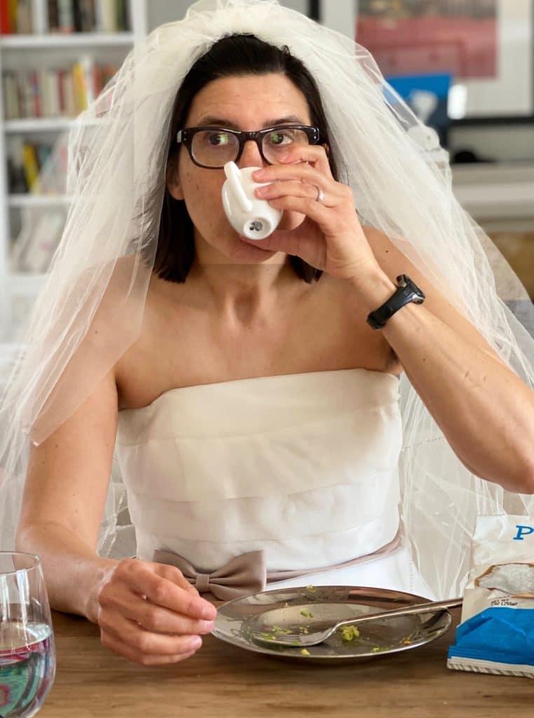 kobieta w sukni ślubnej pije z kubka