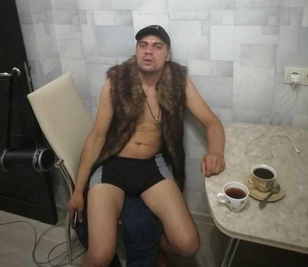 парень в трусах и меховой жилетке в кухне за столом
