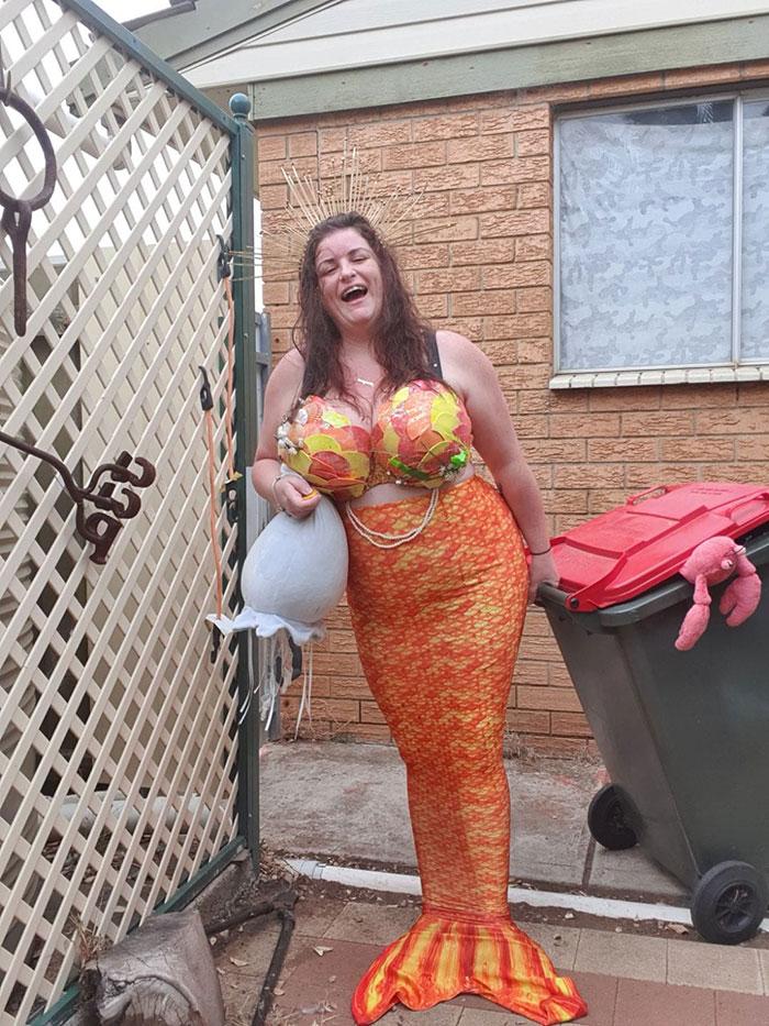 женщина в костюме русалки с мусорным баком