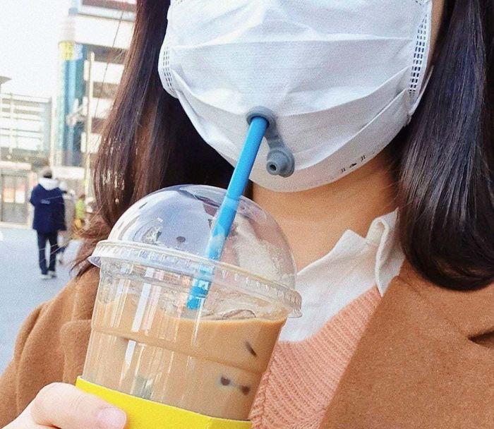 девушка в маске пьет через трубочку