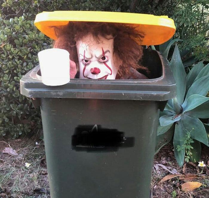 мужчина сидит в мусорном баке