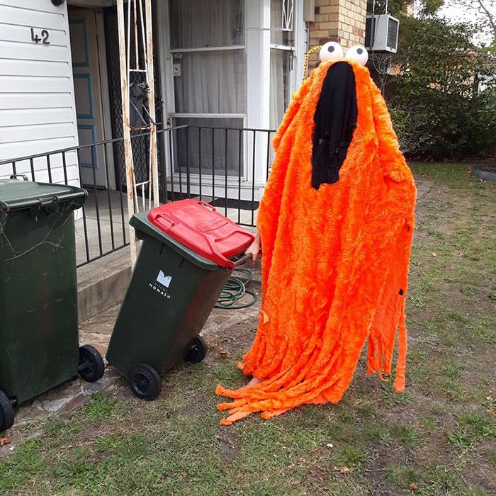 человек в смешном костюме выносит мусор