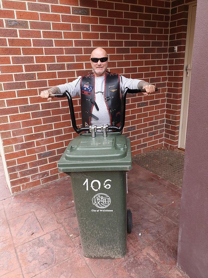 мужчина байкер выносит мусор