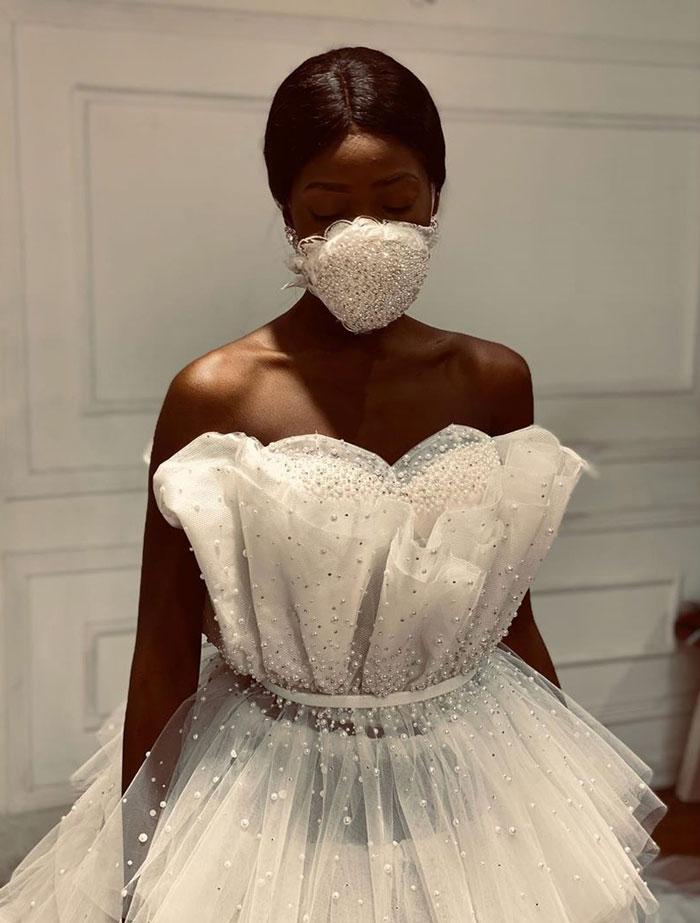 чернокожая девушка в свадебном платье и маске
