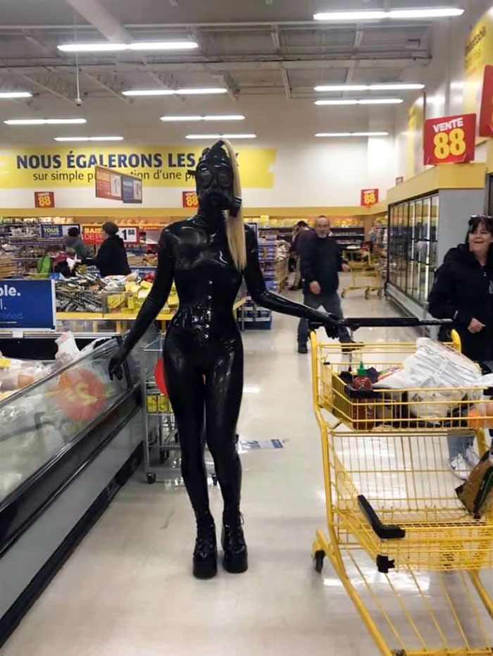 девушка в латексном комбинезоне и противогазе в магазине