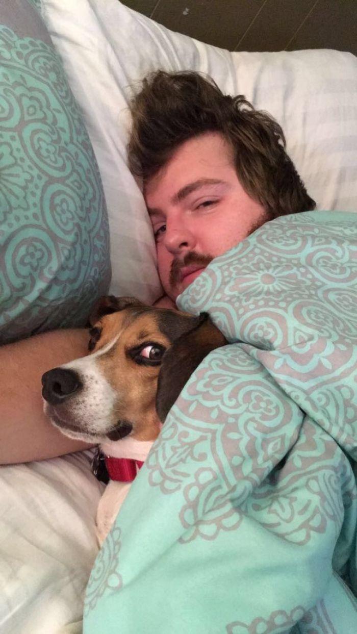 парень лежит с собакой в кровати
