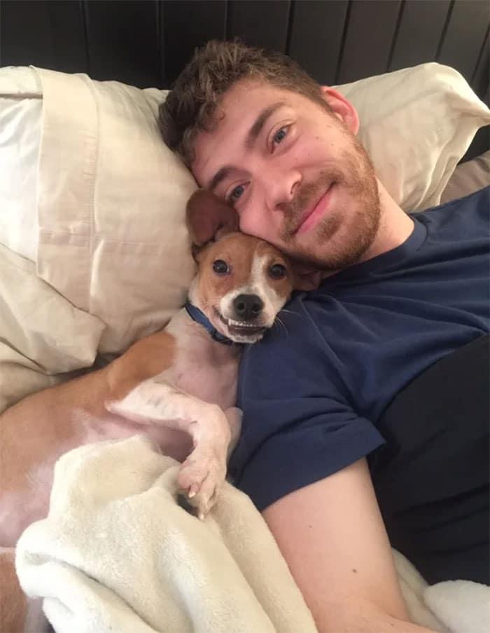 парень с собакой лежат на кровати