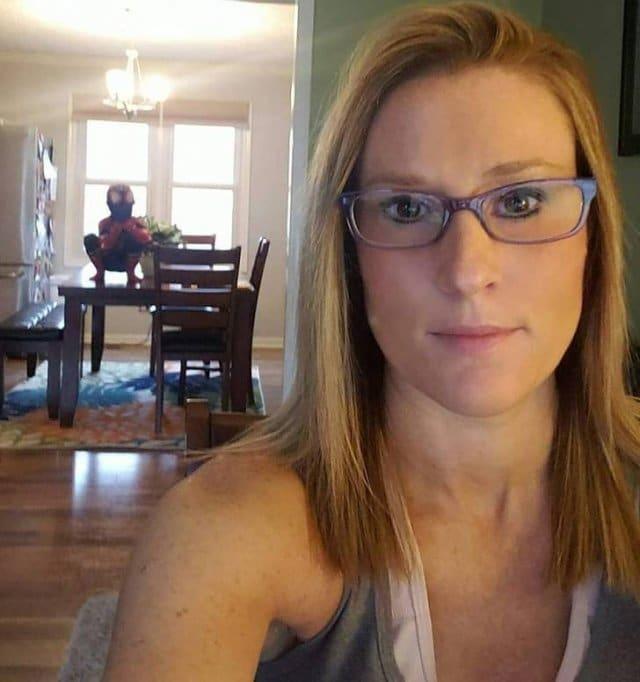 женщина в очках и ребенок на заднем плане