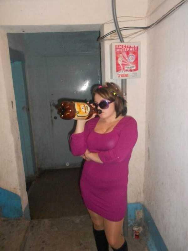 девушка пьет пиво из бутылки в подъезде