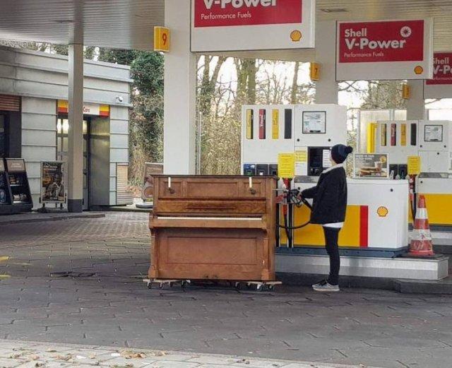девушка заправляет бензином пианино на заправке