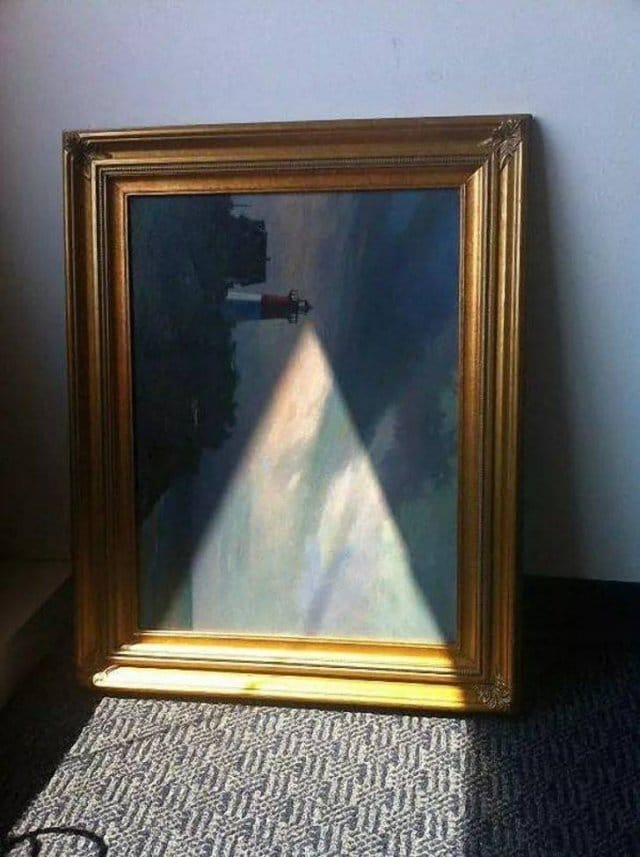 картина с маяком стоит у стены на полу