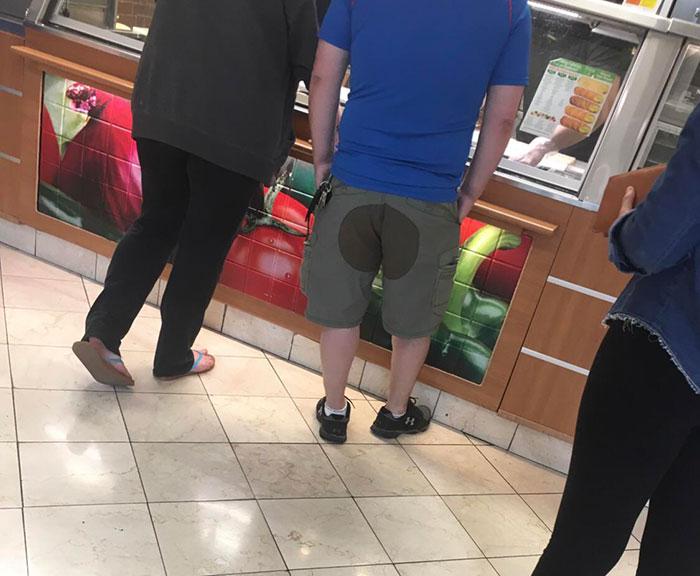 мужчина в шортах с пятном сзади