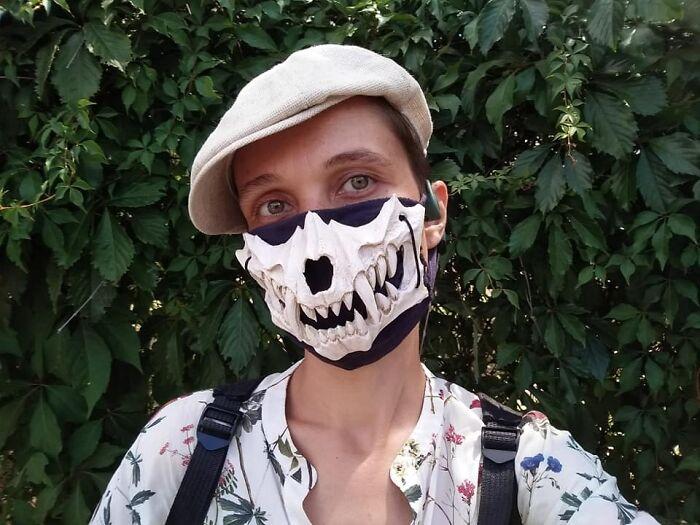 парень в кепке и маске с челюстью черепа