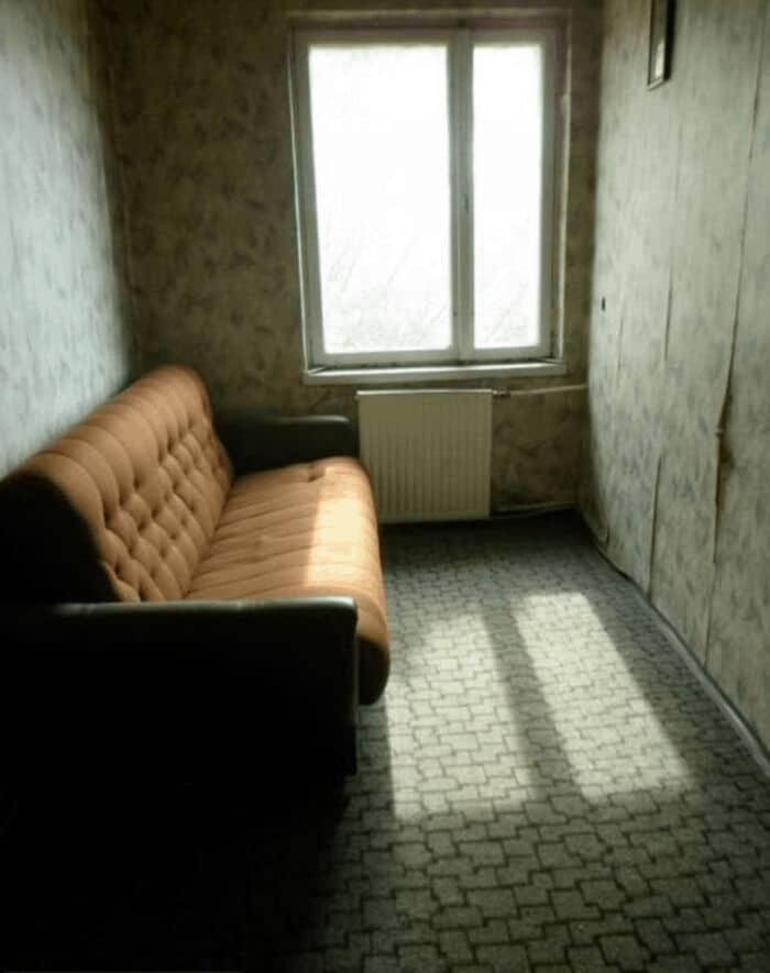 рыжий диван в маленькой комнате