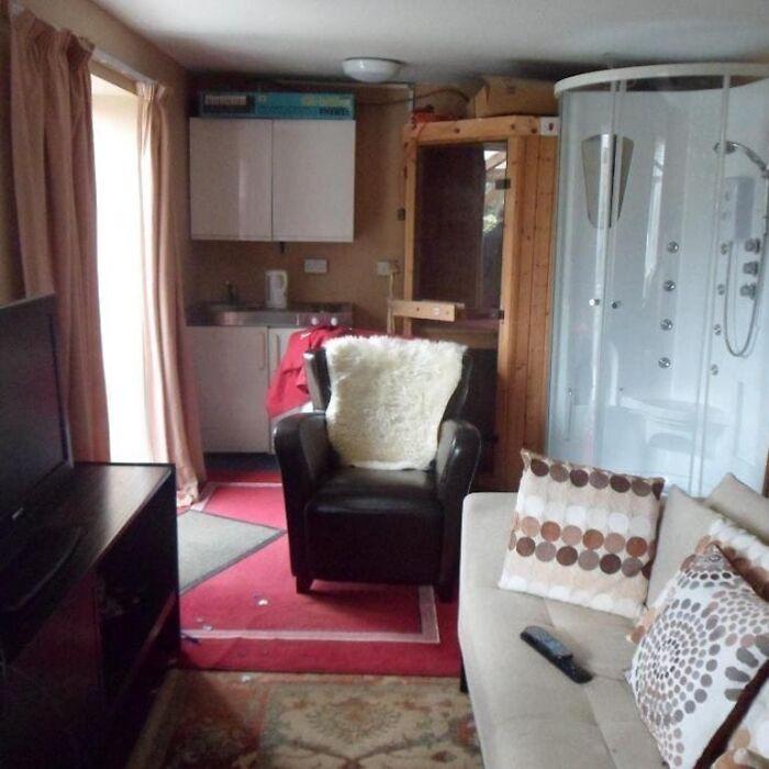 комната с душевой кабиной возле дивана