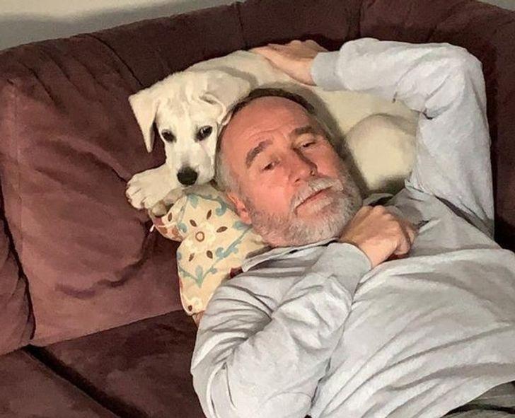 мужчина лежит головой на белом щенке