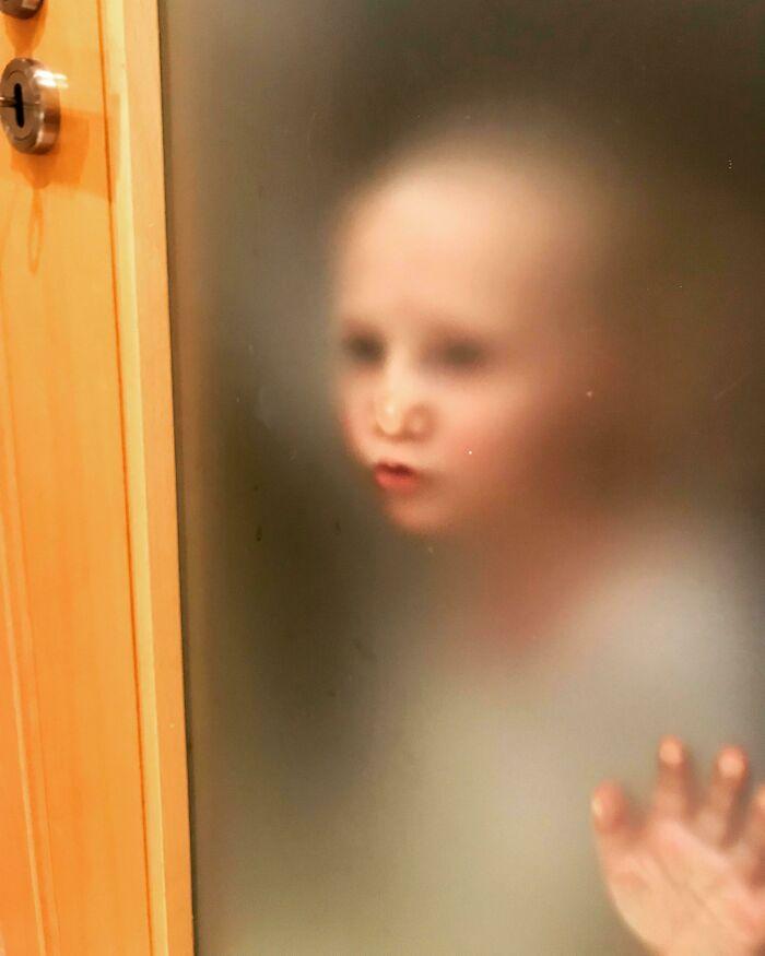 ребенок за стеклянной дверью