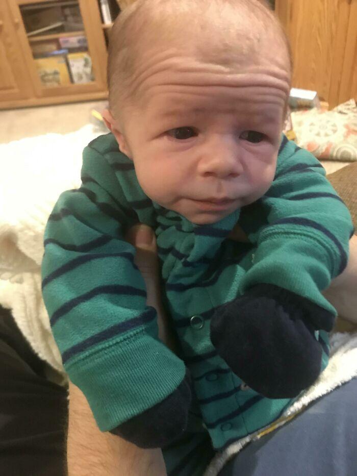 новорожденный в зеленом комбинезоне